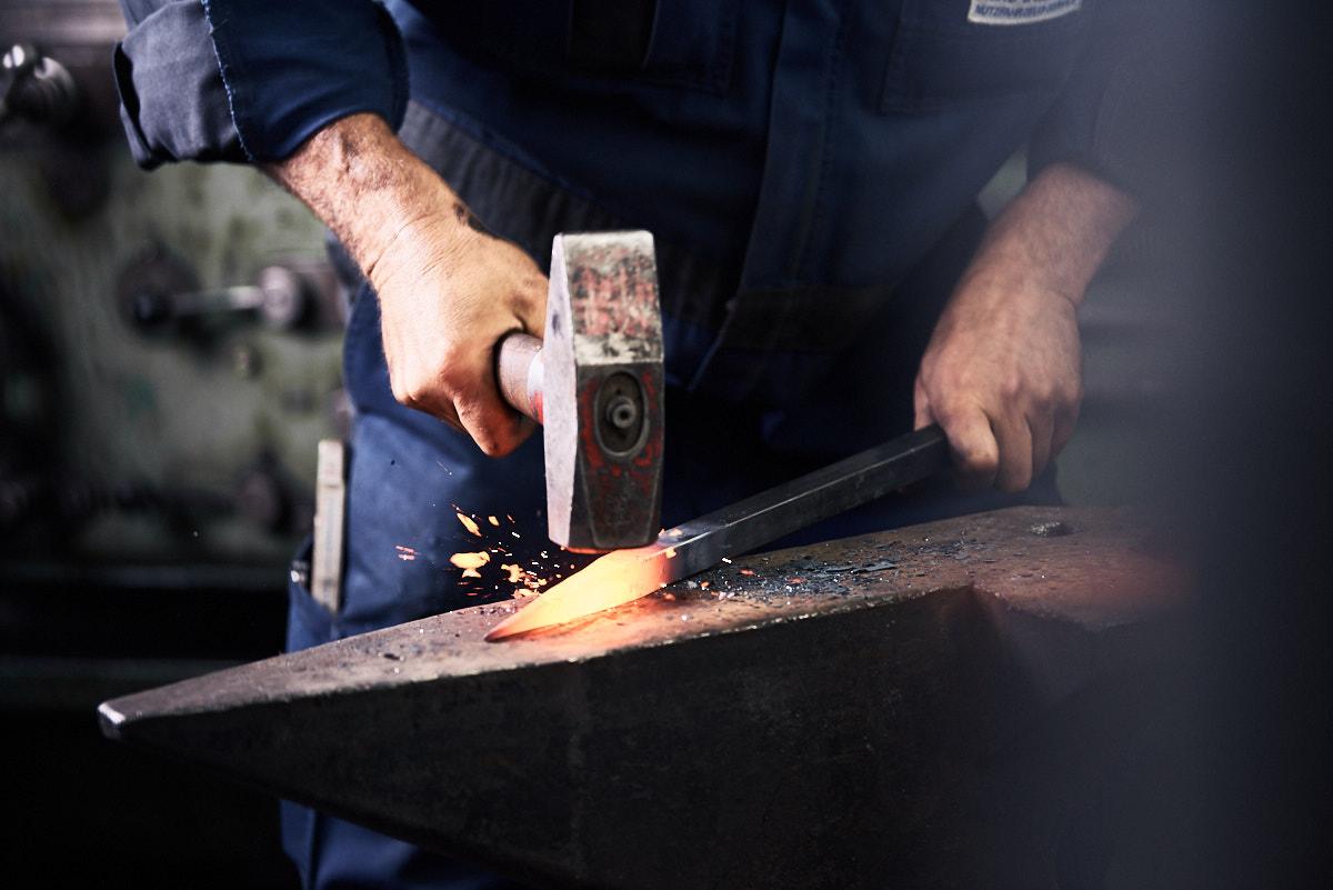 Unternehmensfoto bei der Arbeit, Hand Hammer glühendes Eisen