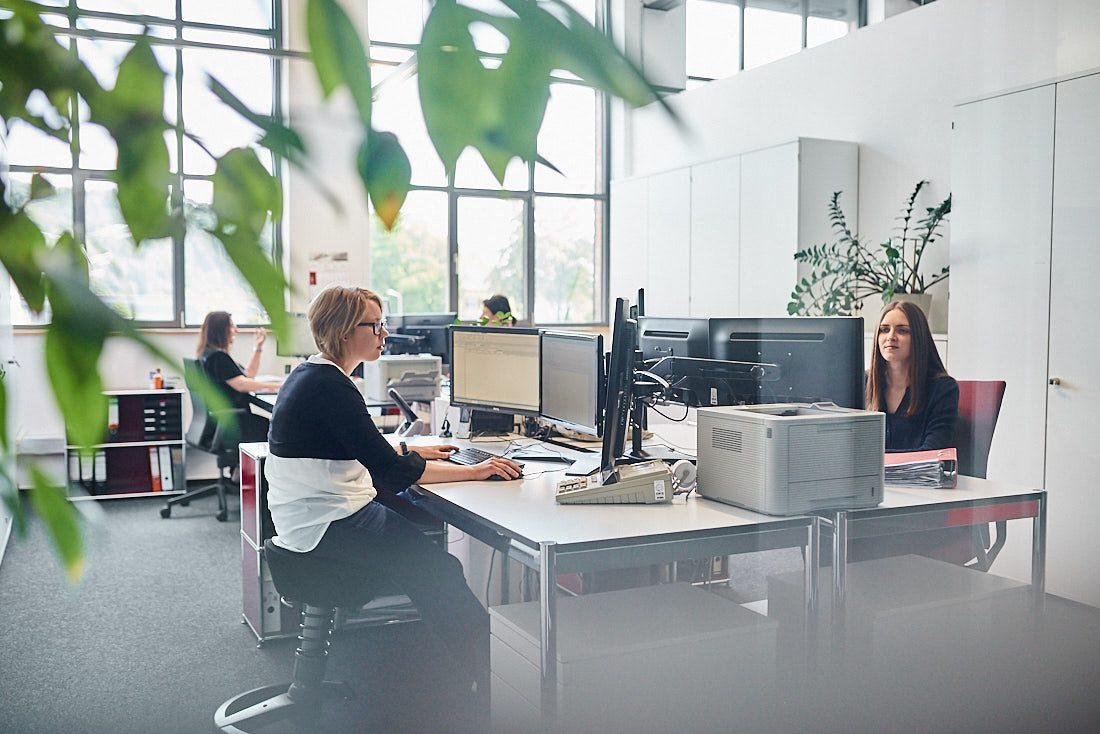 Glasbüro: Business Bild Großraumbüro. Fotograf für authentische und lebendige echte Business Bilder bei der Arbeit