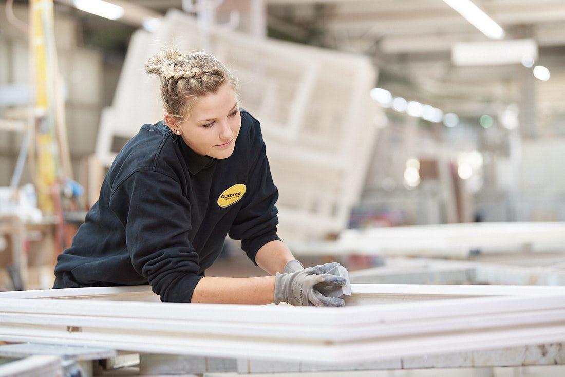 Unternehmensfoto & Businessfoto: Arbeitssituation mit einem Mitarbeiter in der Produktion, mit einem hellen unscharfen Business Hintergrund.