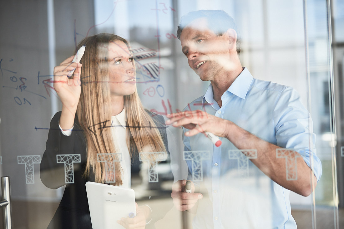 Businessfotografie mit Managern in einem Meeting. Fotografiert mit einem unscharfen Business Hintergrund.